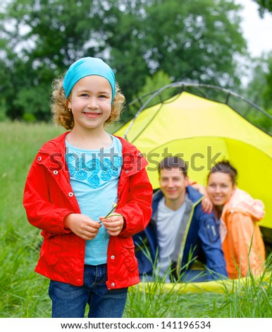 Young girl with his family near tent in camping on the nature - stock photo