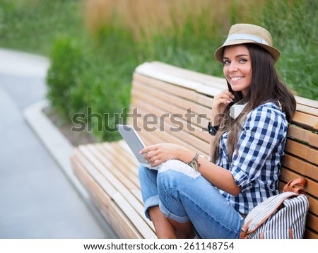 Young girl with laptop on the bench - stock photo