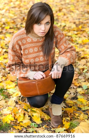 young girl with leather handbag sitting on yellow autumn leaf background