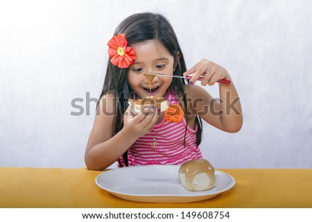 Young girl with long black hair smiles and enjoy while sitting slathering bread with peanut butter - stock photo