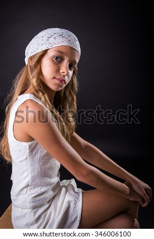 Young girl with long hair and cap sitting with a sober look on a black background - stock photo