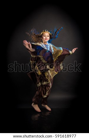 young girl with long hair in oriental dancer costume Khaleej posing and dancing on a black background in the scenic blue light