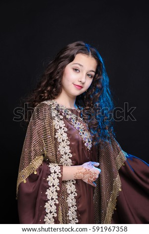 young girl with long hair in oriental dancer costume Khaleej posing on a black background in the scenic blue light