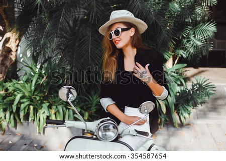 young girl with long hair in sunglasses in a black shirt and jacket with white pants with red lipstick posing on a retro scooter Vespa colors taifani vintage style straw hat with the fields of fashion - stock photo