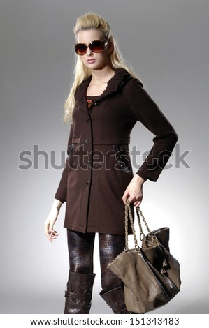young girl with long hair in sunglasses with bag over light background