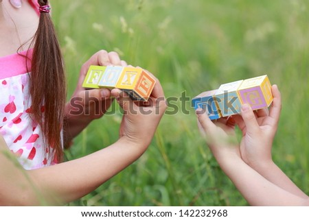 Young girl with long hair sitting in spring grass playing with blocks with letters and form words outdoors