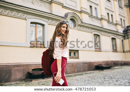 Young girl with long hairstyle and vinous bag is walking in the city. She listening to music and smiling to side.