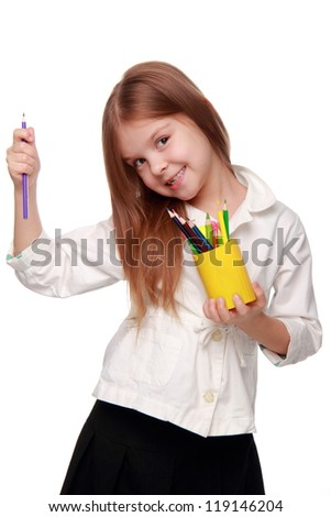 Young girl with lots of pencils smiling happily - stock photo