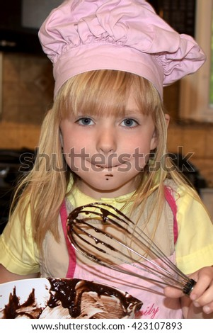 young girl with messy face after licking whisk