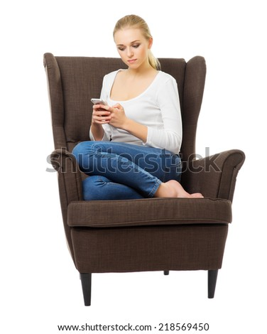 Young girl with mobile phone on chair isolated - stock photo