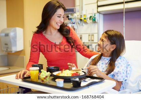 Young Girl With Mother Eating Lunch In Hospital Bed - stock photo