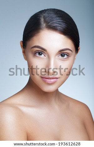Young girl with nude makeup over grey background - stock photo