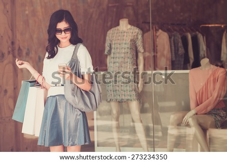 Young girl with paper bags standing at the shop window and text messaging - stock photo