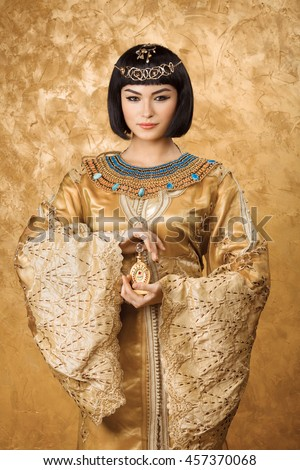 Young girl with perfume bottle. Glamorous closeup portrait of beautiful sexy stylish brunette young woman model with bright makeup with gold jewelery. Cleopatra - stock photo