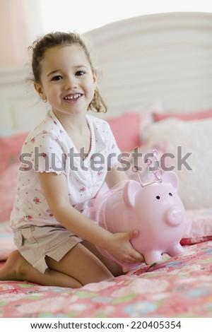 Young girl with piggy bank on bed - stock photo