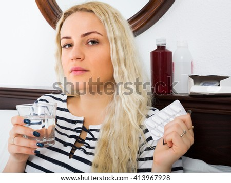 Young girl with pills and headache suffering in bedroom - stock photo