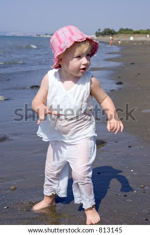 Young girl with pink hat playing on beach on vacation in Spain