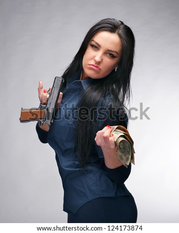 Young girl with pistol and old money on a gray background - stock photo