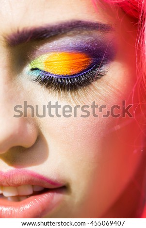 Young girl with pretty face bright professional makeup colorful eyeshadow yellow and orange hair
