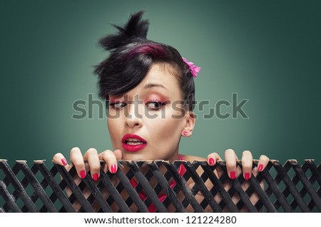 young girl with punk style hair hanging on a fence and watching something - stock photo