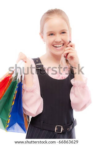Young girl with purchases speaks by phone, isolated on white background.