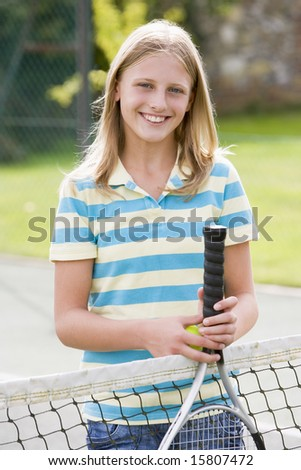 Young girl with racket on tennis court smiling - stock photo