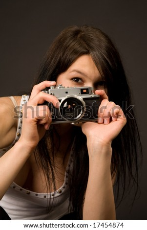 Young girl with retro camera isolated on black background