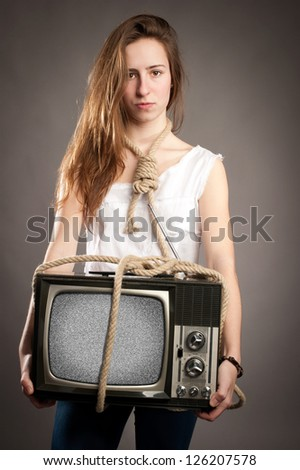 young girl with rope holding retro television - stock photo