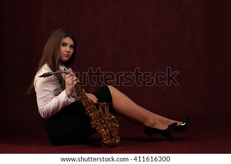 Young girl with saxophone in studio on dark background