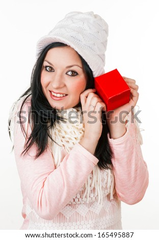 Young girl with scarf and wool hat holding a red gift box