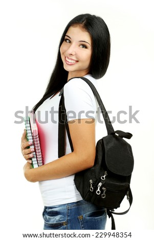 Young girl with school backpack holding notebooks - stock photo