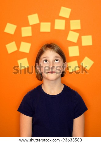 Young girl with sticky notes around her head representing her thoughts - stock photo