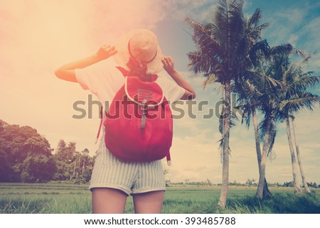 Young girl with straw hat enjoying her trip in nature at sunny day near palm trees (intentional sun glare and vintage color) - stock photo