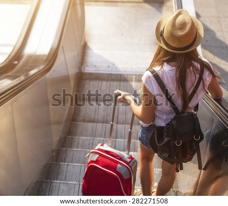 Young girl with suitcase down the escalator. - stock photo