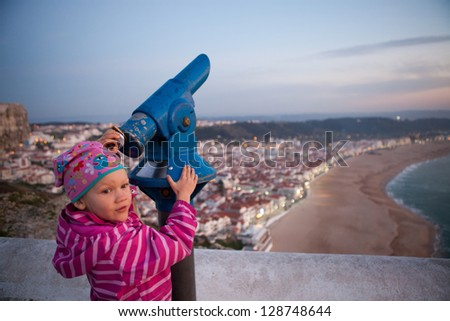 Young girl with telescope in viewing area on cliffs overlooking Nazare Portugal - stock photo