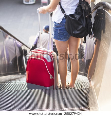 Young girl with the red suitcase standing on the escalator. Travel concept. - stock photo
