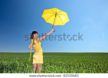 Young  girl with umbrella on a meadow. The polarising filter is used.