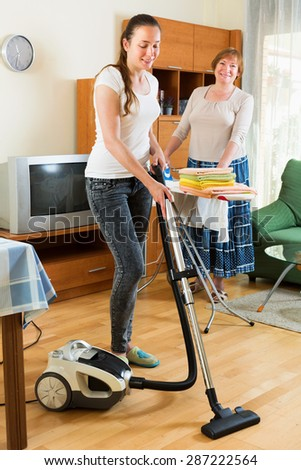Young girl with vacuum cleaner helps her mother do housework  - stock photo