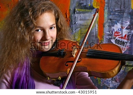 Young girl with violin on color graffiti background - stock photo