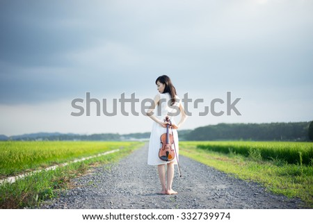 young girl with violin walking down the country road - stock photo