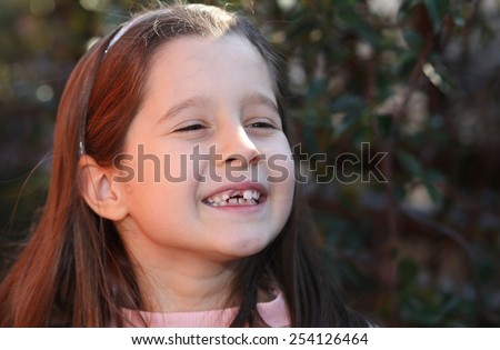 young girl without a tooth while smiling - stock photo