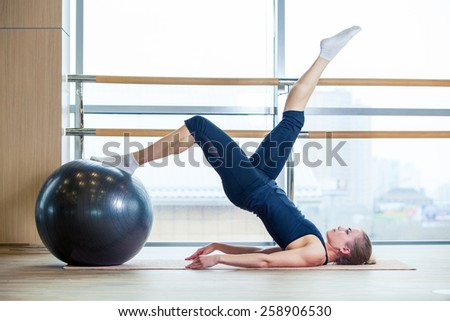 Young girl working out at the gym with a ball. - stock photo