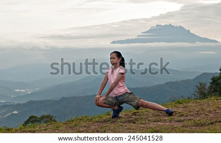 Young girl working out in an early morning with Mount Kinabalu as background. - stock photo