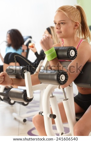 Young girl working out on weight machine at the gym. - stock photo