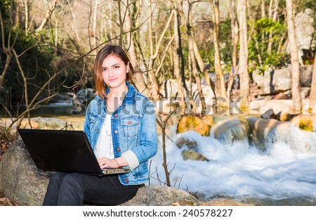 Young girl working with laptop under a tree, enjoying the nice weather