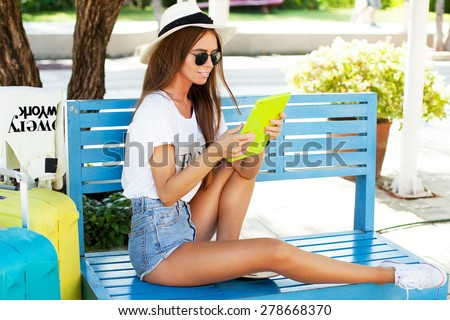 young girl works on the tablet on the internet and goes to the airport.working on tablet in  park,using interenet connection.Summer image,wear hat and summer sunglasses,bright luggage cool accessories - stock photo