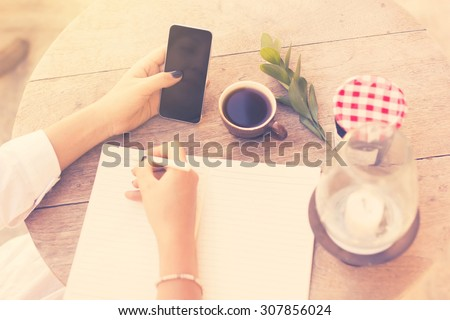 young girl writes in a notebook with cell phone and cup of coffee, vintage photo effect - stock photo