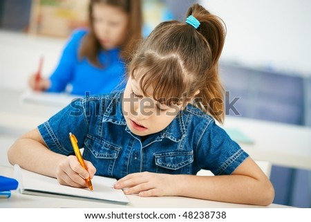 Young girl writing at school sitting in class with other girl in background. - stock photo