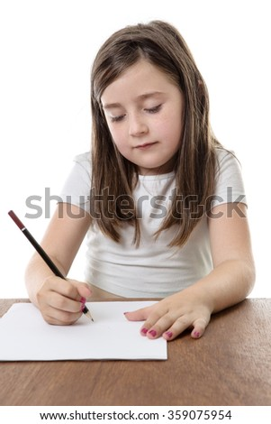 Young girl writing in a book doing her homework