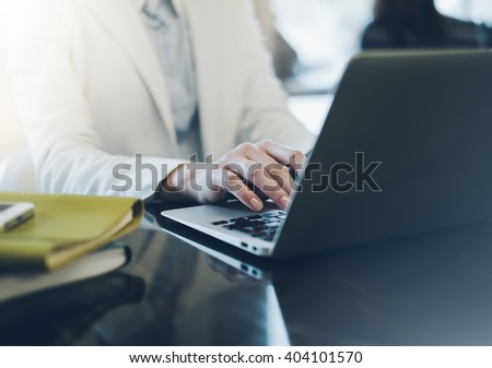 Young girl  writing text hands on the open laptop in a cafe on a table with reflection and glare, businesswoman dressed in a white business suit working on computer, female hands typing on keyboard